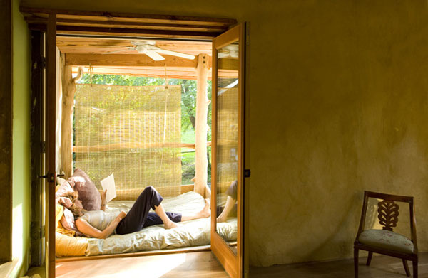 Summer bed on exterior porch with fan and natural ventilation.