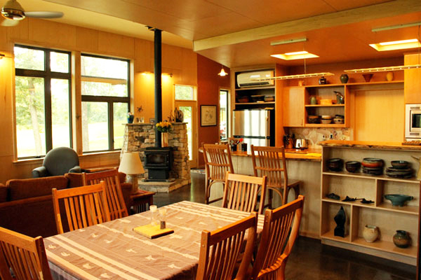 View of dining room and kitchen with masonry stove.