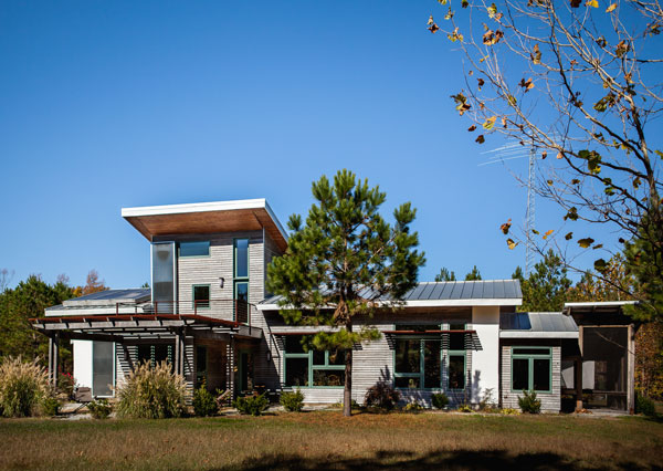 Bob's net zero Home: Back view with large windows, solar panels and trellis.