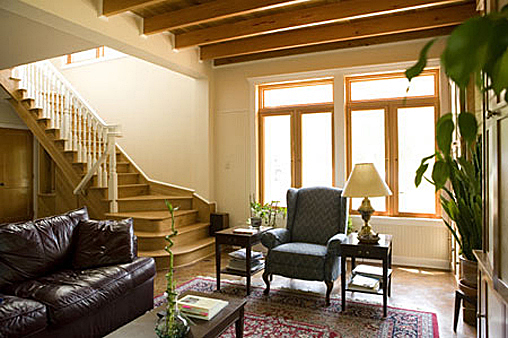 Living room with lots of natural light and wood beams.