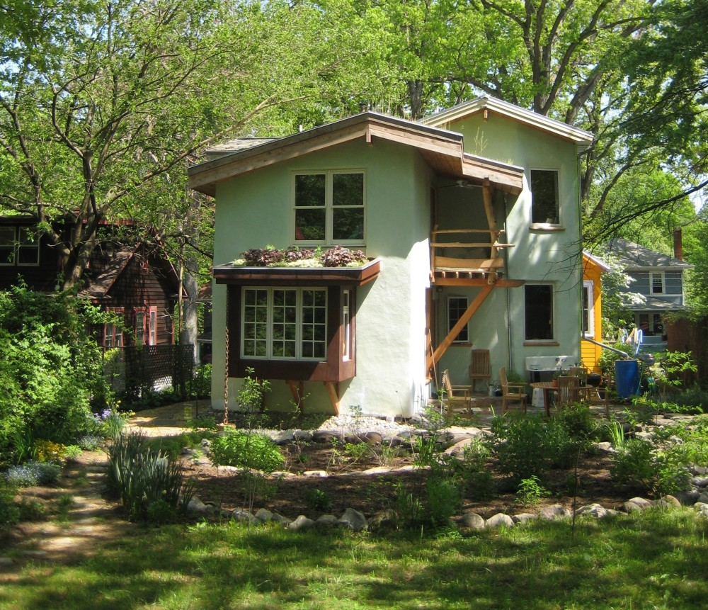 Contact Us - Beth & Bill's Straw bale addition with green roof and sleeping porch looks out into the regenerative landscaped garden.